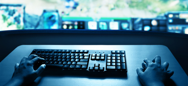 hands typing on gaming keyboard with video game in background