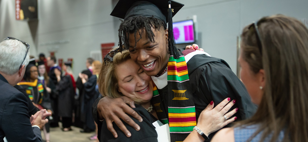 student hugging adult at graudation