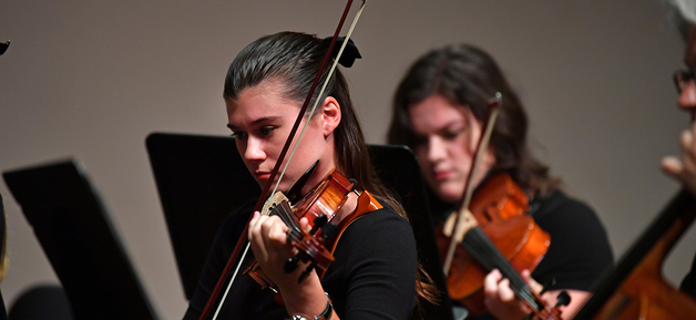student playing violin with band
