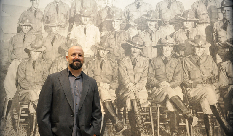 Chris LaPorte standing in front of his massive graphite drawing Cavalry