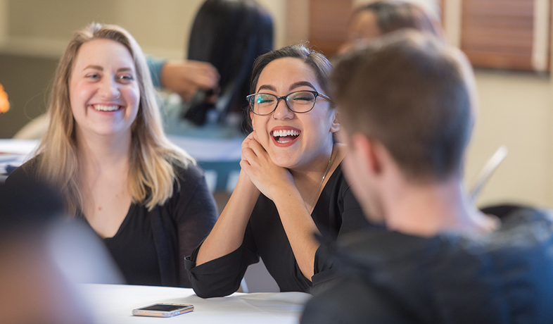 2 students sitting at table talking inside