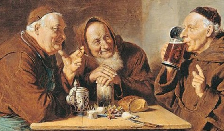 4 men sitting at a table drinking beer