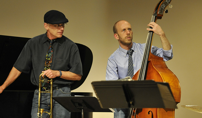 2 faculty members on stage playing instruments