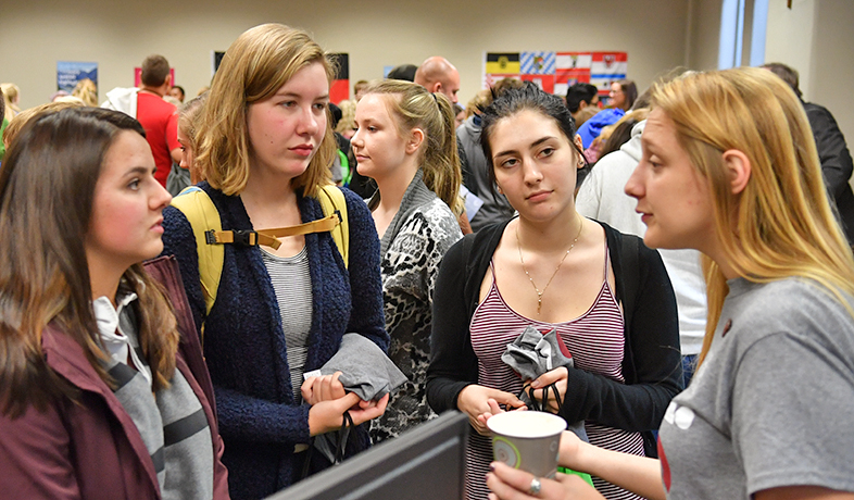 students engaging with women with many other people in the background