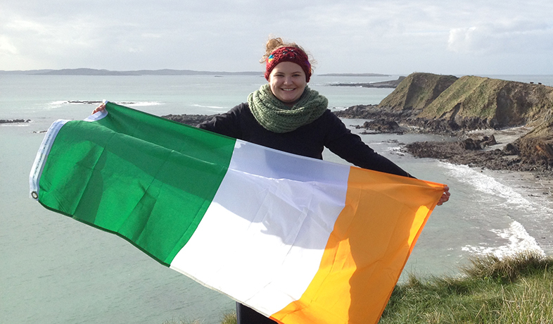student standing on cliff over water holding Irish flag