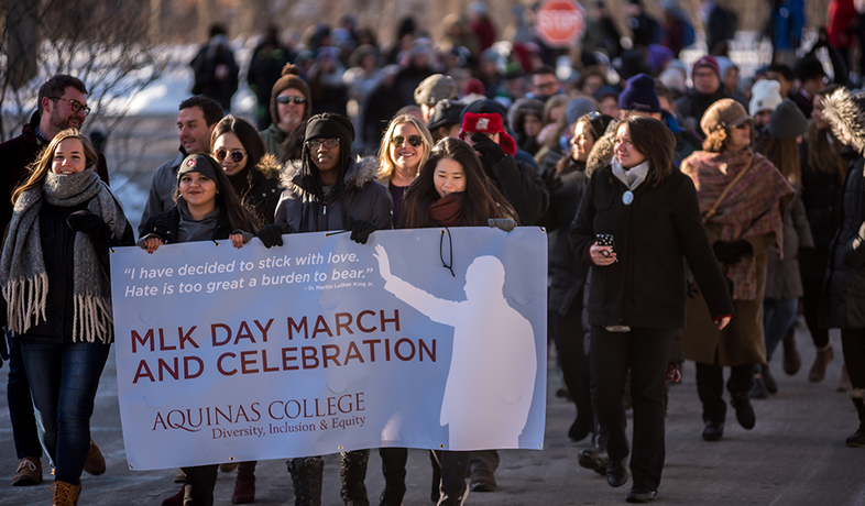 students and employees marching with MLK day sign