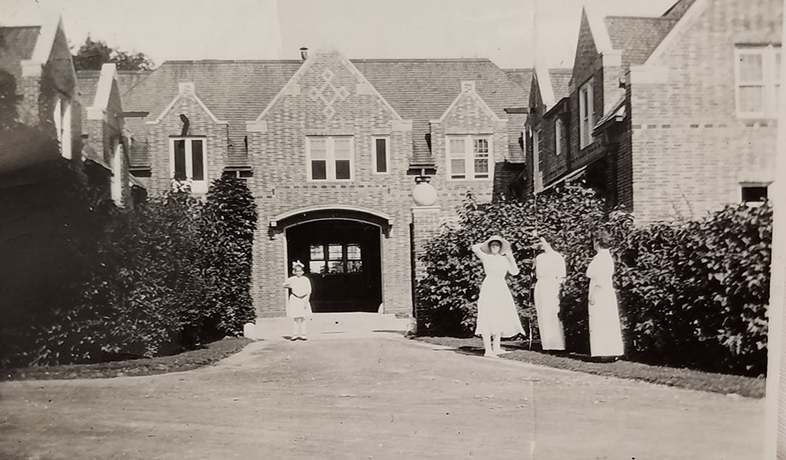 old photo of building on AQ's campus