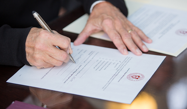 man signing paper with AQ seal on it