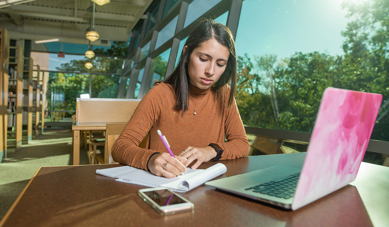 student at desk in the library with notepad and laptop
