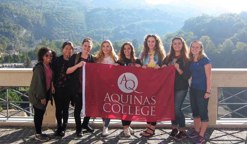 group of students posing with AQ flag