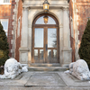 Two white marble lions flanking the door of a brick historical building