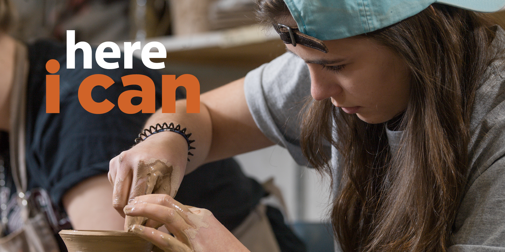"female student making clay pot with ""here i can"" written in image"