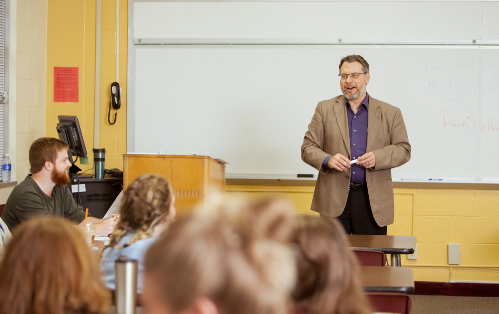 professor talking to students in a classroom