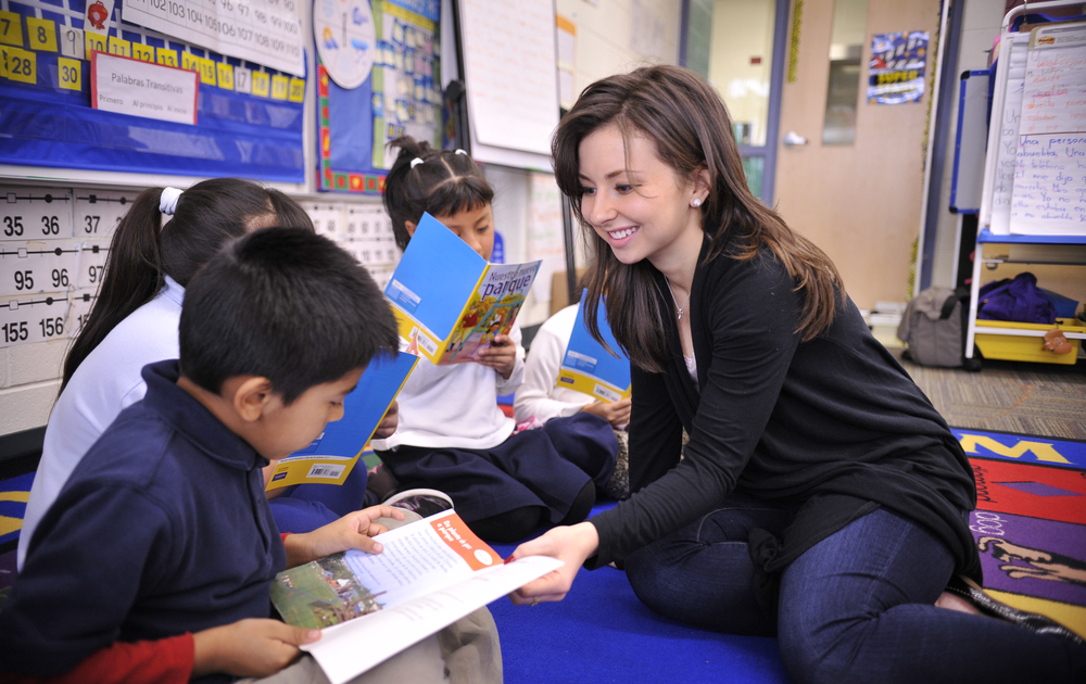 student helping children read in a classroom
