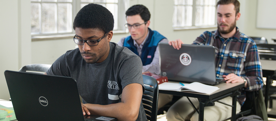 students working on laptops in a classroom