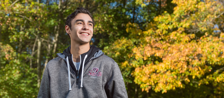 male student looking off camera with trees in the background
