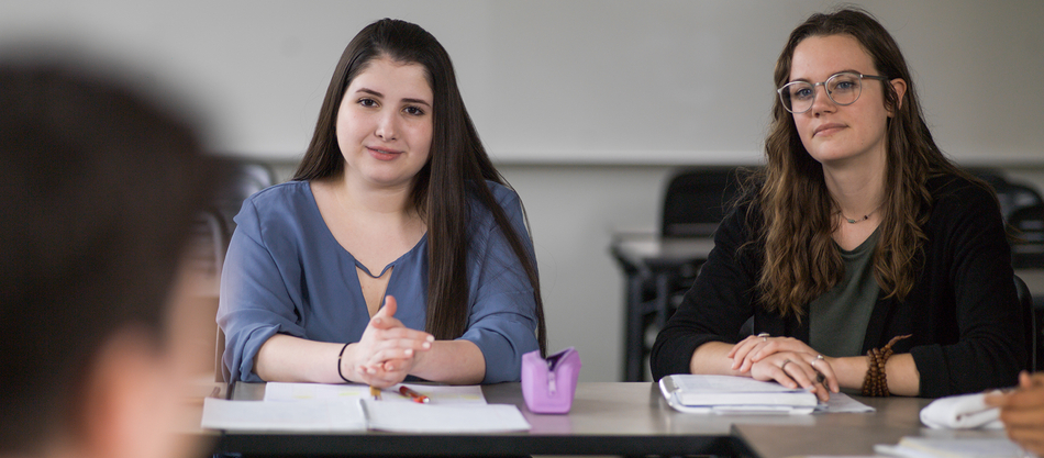two students sitting at table looking at professor