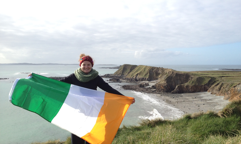 Girl holding Irish flag on a beach in Ireland