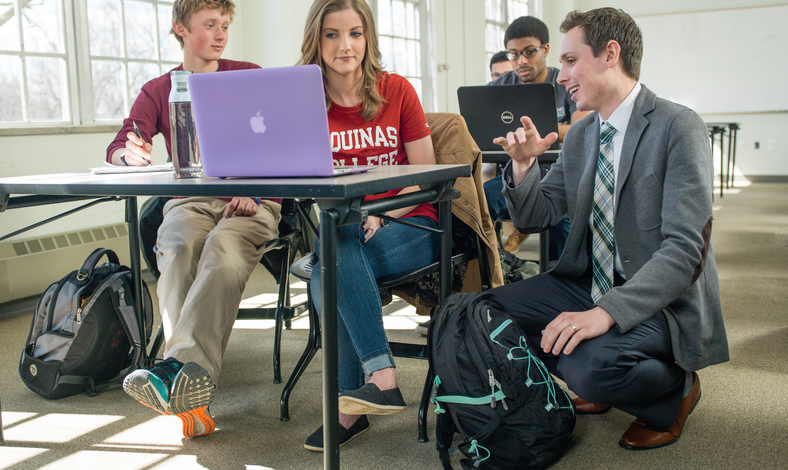 Students listening to professor with a laptop
