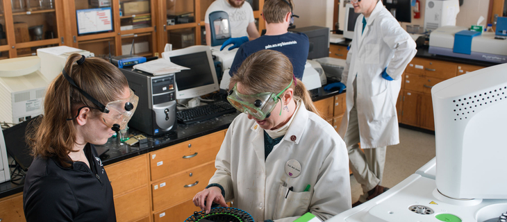 students and professor working on chemistry in a classroom