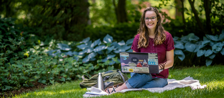 girl sitting in grass with a laptop smiling