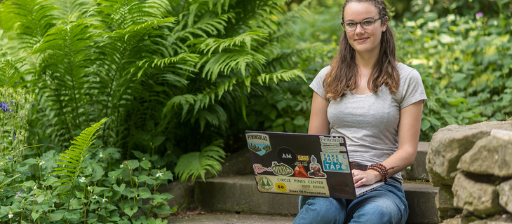 student on steps outside with laptop
