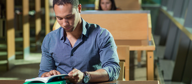 student sitting at large desk reading book