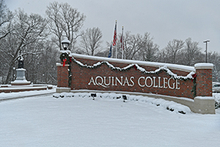 """Aquinas College"" sign with snow"