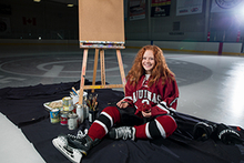 woman in hockey uniform sitting on ice by an easel