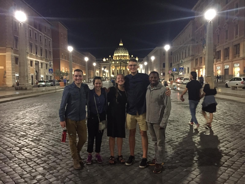 group of students standing on street at night