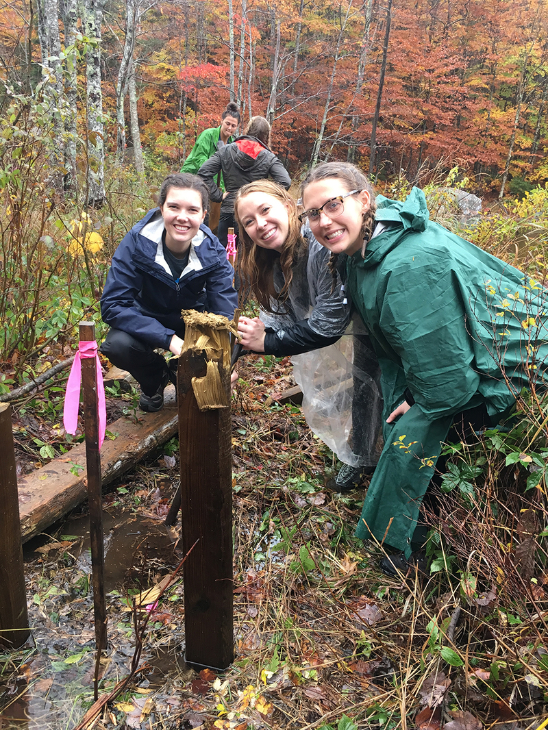 3 students posing around a wooden pole in puddle