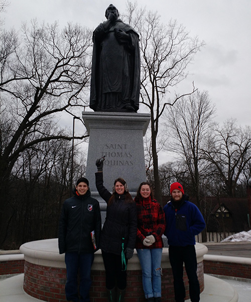 group of students in front of statue