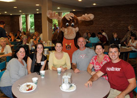 people sitting around a table in the cafeteria with a moose mascot
