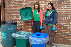 Two students standing by trash, recycle, and compost bins